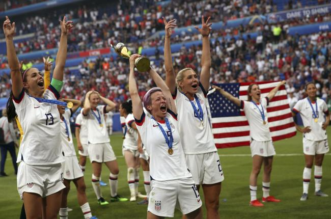 PRIDE: United States star Megan Rapinoe, centre, lifts the Women's World Cup trophy