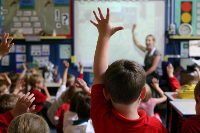 File photo dated 06/07/11 of children at school raising their hands to answer a question as a third of parents think school trips are unaffordable, while many others think the costs of uniforms and equipment are too high, a poll suggests. PRESS ASSOCIATIO