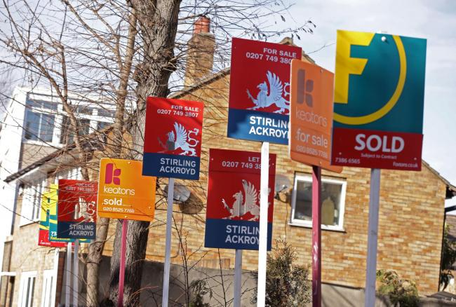 File photo dated 01/03/15 of a row of estate and letting agent signs displayed outside houses in Clapton, east London. Research suggests over-priced properties can languish on the market for around two months longer than homes which have been given a more