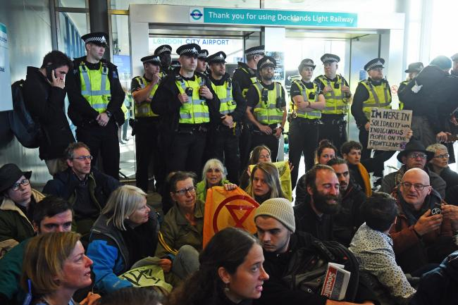 Police officers watch as activists stage a blockage of the exit from the Docklands Light Railway to City Airport