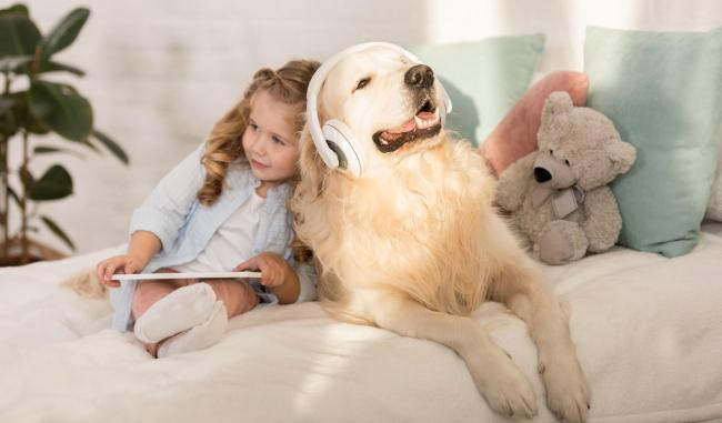 Child with a dog listening to music