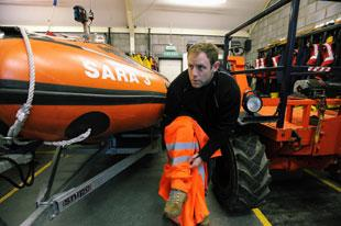 SARA crew volunteer Deano Paget gets rigged up in an orange suit used for emergency occasions at the training depot near the old Severn bridge in Chepstow