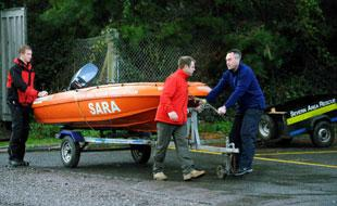 SARA crew members from left Ben Morgan, Deano Paget and Dave Thompson unload a small boat from the training centre near the old Severn bridge in Beachley in Chepstow