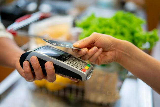 Close up of unrecognizable customer doing a contactless payment at the supermarket **DESIGN ON CREDI CARD WAS MADE FROM SCRATCH BY US**.