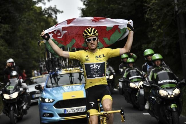 Britain's Geraint Thomas, wearing the overall leader's yellow jersey, holds the flag of Wales during the 21st and last stage of the 105th edition of the Tour de France cycling race between Houilles and Paris Champs-Elysees, Sunday, July 29, 2018.