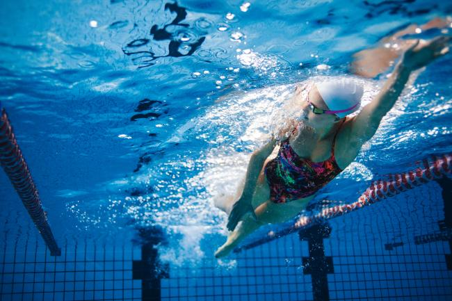 Underwater shot of fit swimmer training in the pool. Female swimmer inside swimming pool..