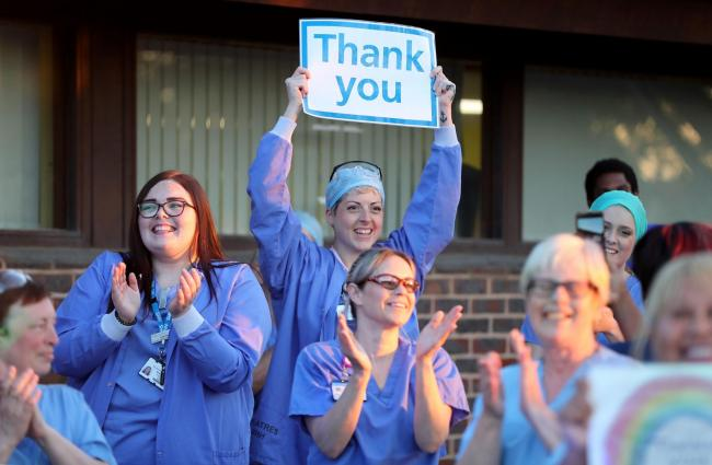 CHEERS: Medical workers join in the applause to salute health and care staff during a weekly Clap for Carers event. Picture: Gareth Fuller/PA Wire