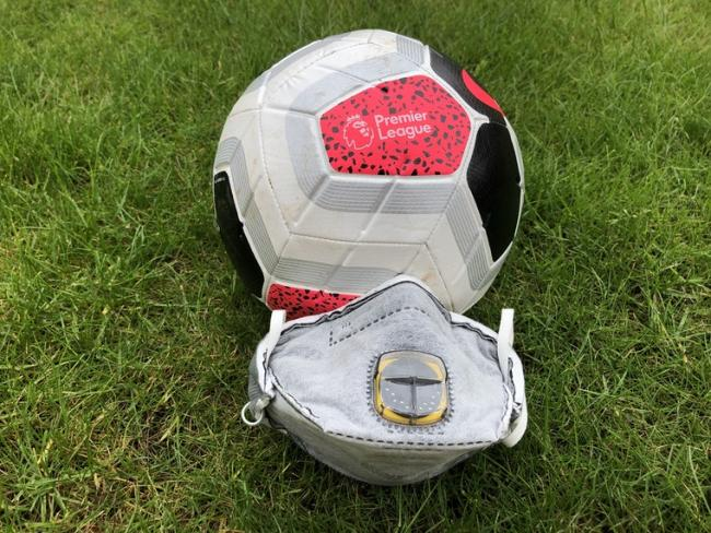 A Premier League Football next to an FFP2 face mask. Picture: PA Wire