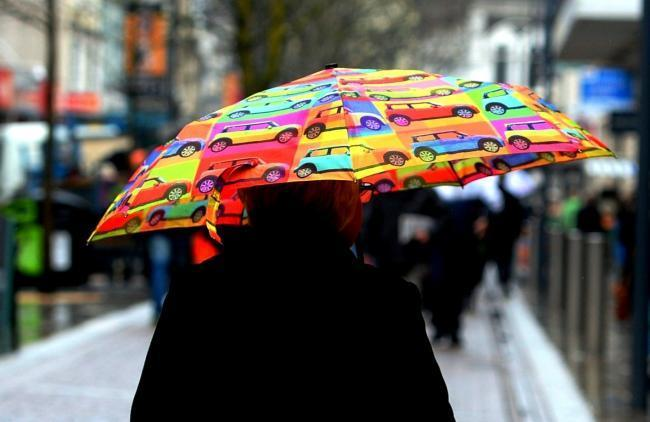 A woman holds an umbrella on Commercial Street, Newport.