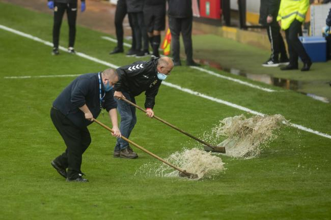 10.10.20 - Cambridge United v Newport County - Sky Bet League 2 - Grounds men sweep the waterlogged areas of the pitch at half time Picture: Huw Evans Agency