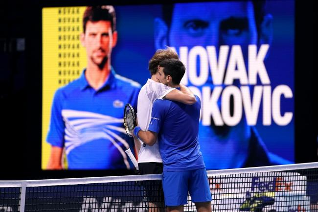 Novak Djokovic (right) embraces Alexander Zverev after their match at The O2