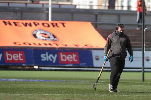GRAFT: A member of ground staff working hard on the Rodney Parade pitch