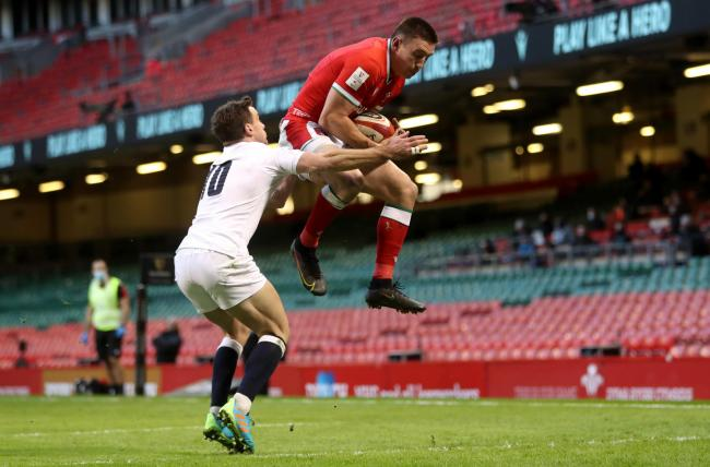 Wales' Josh Adams catches a high ball under pressure from England's George Ford before scoring his sides first try with Jonathan Davies during the Guinness Six Nations match at the Principality Stadium, Cardiff. Picture date: Saturday February