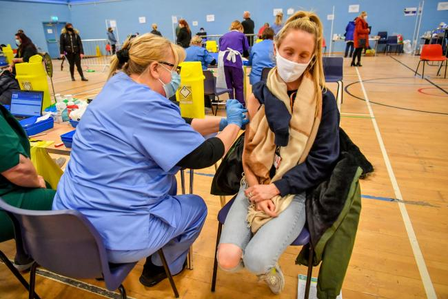 A woman receives an injection of the Pfizer vaccine at a coronavirus vaccination centre set up at Cwmbran Stadium. Picture: PA