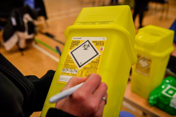 South Wales Argus: Notes are written on a sharps box for used syringes where injections of the Pfizer vaccine are given to the public at a coronavirus vaccination centre set up at Cwmbran Stadium. Picture: PA