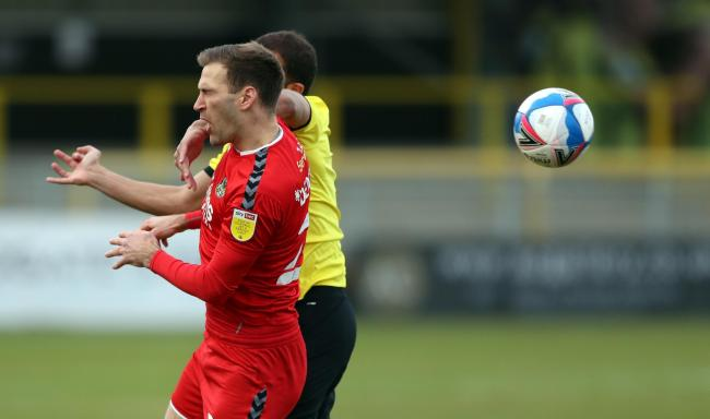 CLATTERED: Newport's Mickey Demetriou is caught by Harrogate's Aaron Martin