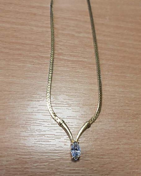Gold necklace with clear stone pendant