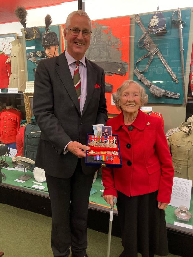 South Wales Argus: Lord Lieutenant for Gwent Brigadier Robert Aitkin and Joan Reynolds with medals and photographs of Lyndon Sheedy at the Royal Regiment of Wales Museum