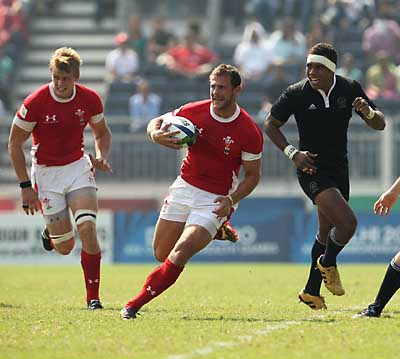 Outclassed: Ifan Evans bursts through, with Cross Keys' Jevon Groves in support, but Wales were thrashed by New Zealand