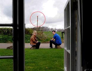 RUINED VIEW: Residents Diane Collins and Ian Harding, with a post and markers (circled) showing the height of the proposed hedge (lower mark) and the top of the panels (upper mark).