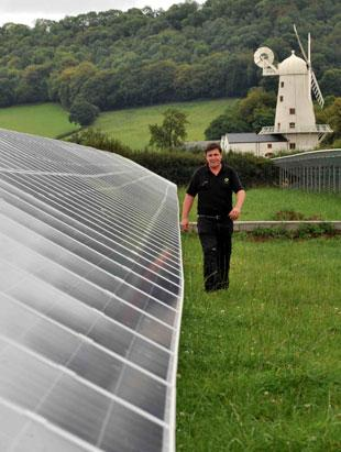 OLD POWER AND NEW: Solar farm boss Paul Hunter with the solar panels and Llancayo windmill, near Usk, in the background