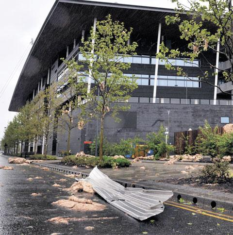 DAMAGED: Debris is scattered across the road from the roof of the university's Newport City Campus building