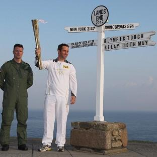 THE JOURNEY BEGINS: Ben Ainslie holds the Olympic Torch as he begins the first leg of the relay (Chris Radburn/LOCOG/PA Wire)