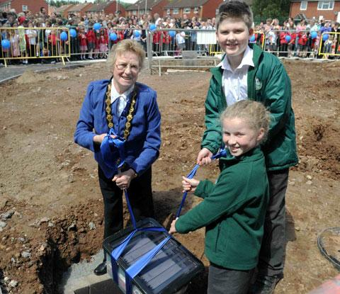FUTURE GIFT: Chairman of Monmouthshire County Council councillor Maureen Powell and Green Lane school pupils Carl Fielding and lauren burns, both 10, lower the time capsule