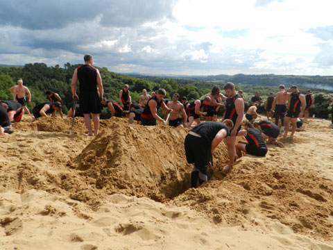 TEAMWORK: The Dragons dig a 'logo' at the top of the 'Big Dipper', the monstrous sand dune at Merthyr Mawr