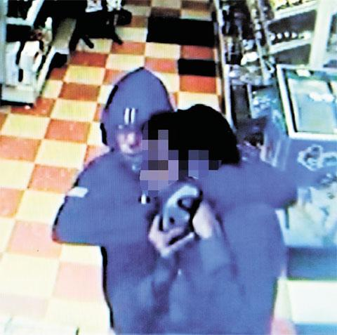 TERRIFYING: Benjamin Sicolo, captured on CCTV holding a knife to the throat of shopkeeper Rashid Ghaffar