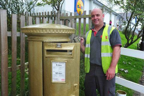 The finishing touches are put on the gold post box