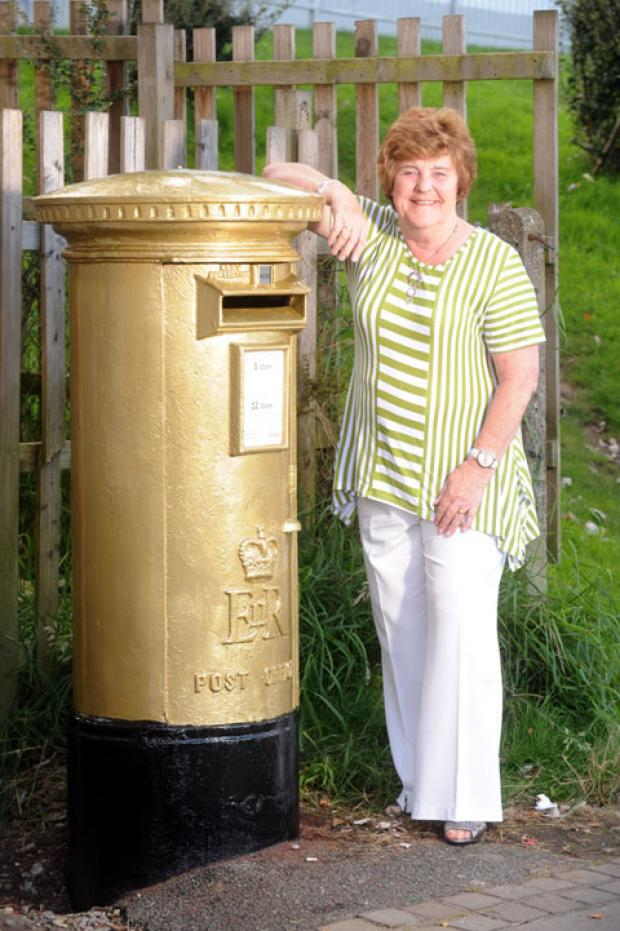 Margaret Colbourne with her son's gold postbox in Tredegar