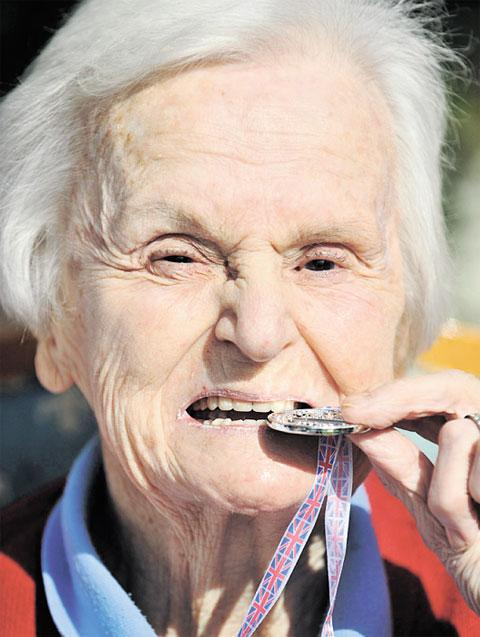 Ann Lees tests out her medal in the traditional way