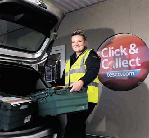 CAR BOOT SALE: Tesco customer assistant Grace Phillips loads a customer's car at the new drive-through shopping facility at the store in Spytty, Newport