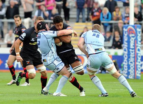 TOUGH DAY: Dragons No 8 Toby Faletau is kept quiet by the Blues defence