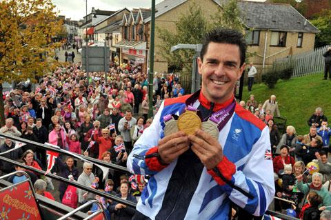 Mark Colbourne shows off his medals on the open-top bus