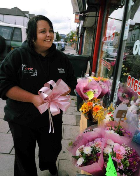 SUPPORT: Lauri Turnbull of LT's on Chepstow Road puts up pink ribbons in of the search for the missing girl April Jones