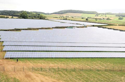 South Wales Argus: EXPANSION BID: A worker (bottom left) is dwarfed by solar panels at the 32-acre farm at Llancayo