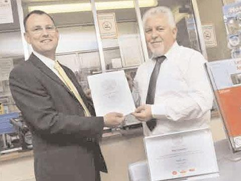 LONG SERVICE: Neil Jenkins, Post Office regional manager gives Swffryd postmaster Nigel Saunders his award for 30 years service