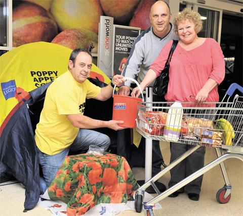 HANDY FOR THE SHOPPING: Andrew Cobley, who camped at Tesco Extra at Spytty, Newport, collects a donation for the Poppy appeal from Richard and Key Hyde