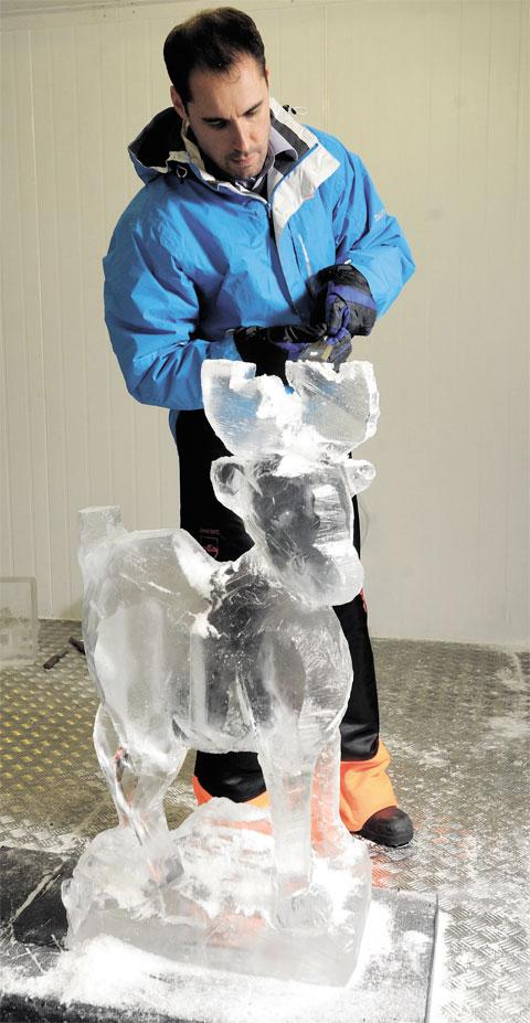 ICE MAN: Reporter Charles Booth tries his hand at ice sculpting, shaving ice to make a reindeer