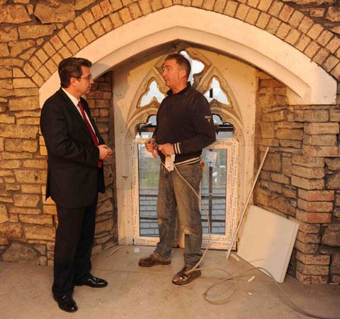 Housing minister Huw Lewis talks to electrician Howard Francis