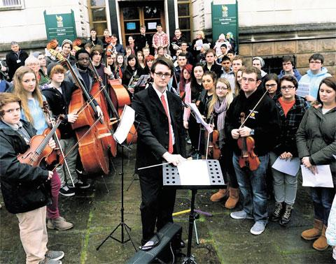 IN UNISON: Ben Teague and others opposed to the cuts stage a musical demonstration outside Newport Civic Centre