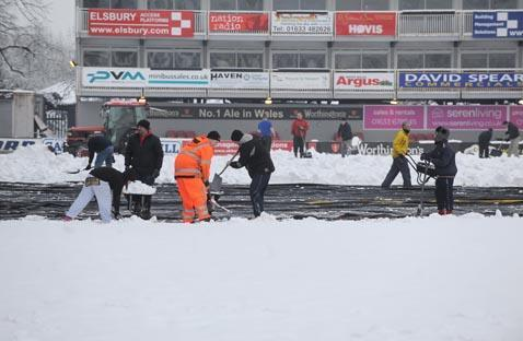 Fans clear snow at Rodney Parade