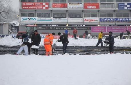 Staff and fans clearing the pitch at Rodney Parade today