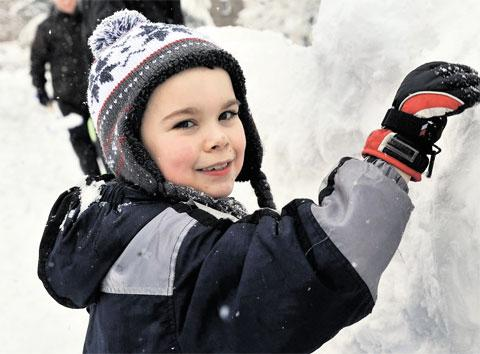 ICE WORK: Zak Roynon- Griffiths, 7, helps build an igloo at the 'Torfaen Play Snow Day' in Abersychan