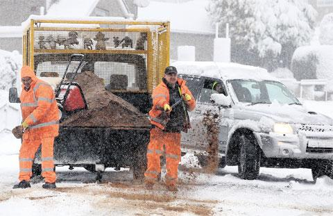 HELPING HAND: Newport Council workmen turned out in the blizzards to use grit to help free a motorist on Gaer Road, Newport