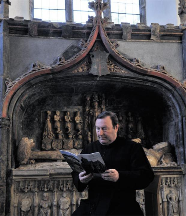 SUCCESS: The Rev Mark Soady with the guidebook in front of the tomb of Sir Richard Herbert inside St Mary's Priory Church