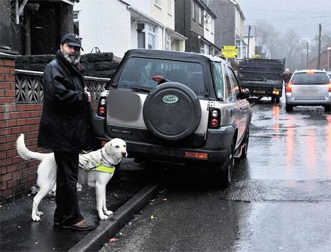 South Wales Argus: 'UNWANTED BARRIER': Tony Harris, with his guide dog Neal, wants to raise awareness of the dangers of parking on pavements