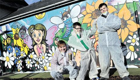 COLOURFUL: Trainee youth worker Kelly Christopher, 19, with kids Connor Weston, 12, and Alex Phillips in front of the mural in the new sensory garden